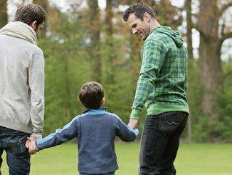Same sex parents with boy in park